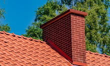 Chimney On The Roof Covered With Red Tiles