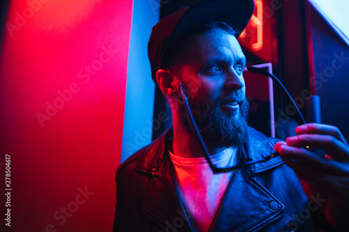 Fototapeta Hipster handsome man on the city streets being illuminated by neon signs. He is wearing leather biker jacket or asymmetric zip jacket with black cap, jeans and sunglasses. obraz