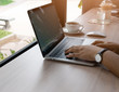 Close-up image of a business woman's hands are using Laptop computer on wood table in coffee cafe, business concept. design with copy space, soft focus.