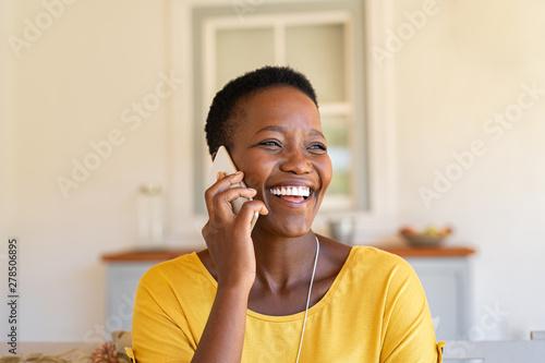 Fototapeta Woman laughing while talking on phone