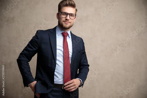 Fototapeta Positive businessman adjusting his tie and standing obraz