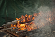 Barbecue Fries In The Coals. Meat And Beef At The Field Kitchen Festival. Fried Meat On An Iron Tray On The Table.