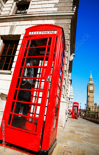Papiers peints Rouge, noir, blanc Iconic Red Telephone Booth and Big Ben Clock Tower over blue sky.