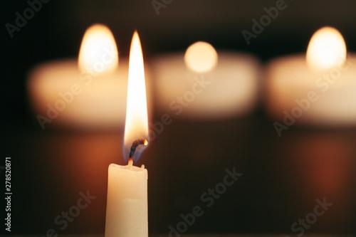 Obraz na plátně  A single burning candle isolated with black background