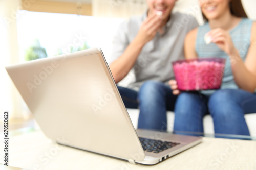 Couple watching online tv movie on laptop at home