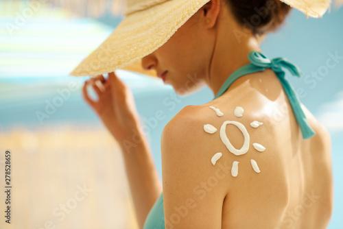 Obraz Woman tanning at the beach with sunscreen cream - fototapety do salonu