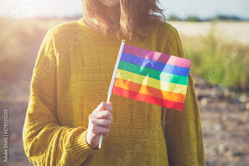Fotomural  young woman wearing yellow sweater holding lgbt rainbow flag outside, same sex c
