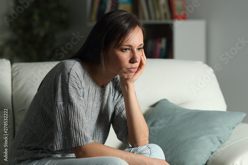 Photo Serious pensive woman looks away at home in the night