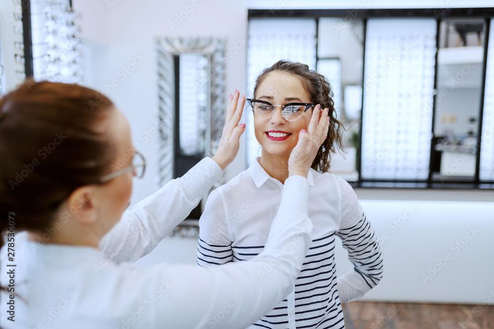 Fototapeta Female optician putting eyeglasses on beautiful Caucasian smiling brunette. Optician shop interior.