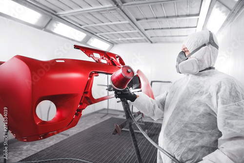 Male worker in protective clothes and mask painting car using spray paint Wallpaper Mural
