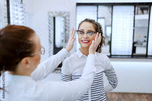 Fotomural  Female optician putting eyeglasses on beautiful Caucasian smiling brunette