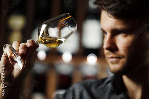 Bokal of white wine on background, male sommelier appreciating drink - 278534668
