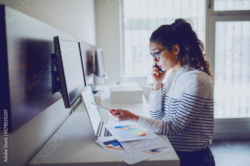 mata magnetyczna Side view of serious businesswoman talking on the phone while pointing with pen at laptop. Office interior. Data analyzing concept.