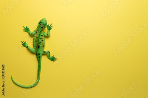 Green lizard toy on bright yellow background фототапет