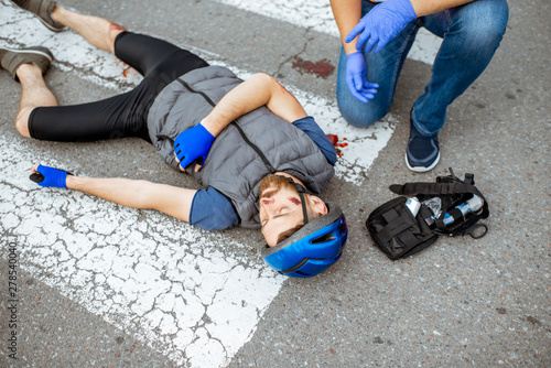 Obraz na plátně  Road accident with injured cyclist lying on the pedestrian crossing near the bic