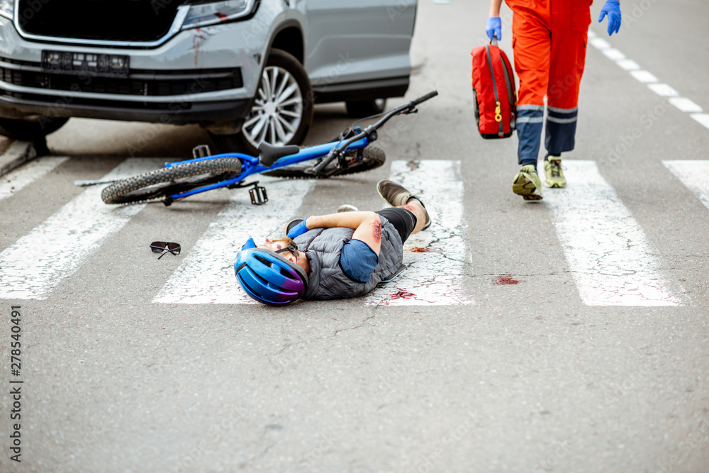 Fototapety, obrazy: Road accident with injured cyclist lying on the pedestrian crossing, medic going to apply first aid