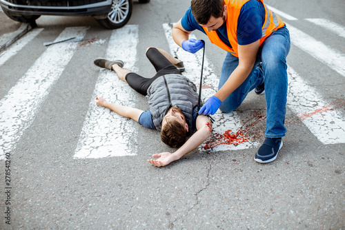 Photo Man applying first aid to the injured bleeding person, wearing tourniquet on the