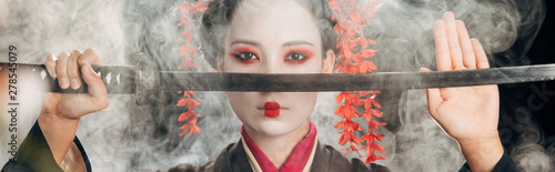 selective focus of beautiful geisha in black kimono holding katana in smoke, panoramic shot