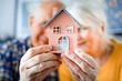 Leinwanddruck Bild - New house concept, happy senior couple holding small home model