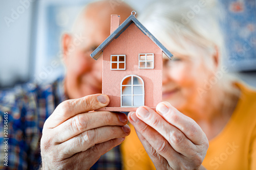 New house concept, happy senior couple holding small home model Billede på lærred