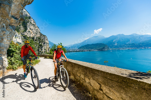 Carta da parati Cycling woman and man riding on bikes at sunrise mountains and Garda lake landscape