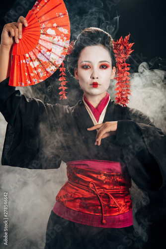 beautiful geisha in black kimono with flowers in hair holding hand fan and gesturing in smoke