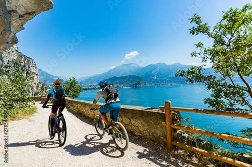 Cycling woman and man riding on bikes at sunrise mountains and Garda lake landscape Fotobehang
