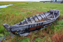 An Old Wooden Fishing Boat Destroyed By Time Lies Not Far From The Water In The Field
