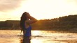 playful girl splashes her long hair in a refreshing summer evening near tropical island with refreshing river water. girl flips back hair. beautiful spray of water in rays of sunset. splash of water
