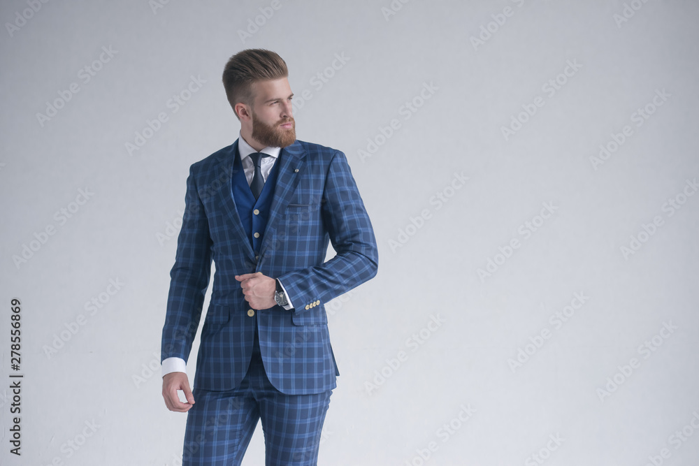 Fototapeta Style in motion. Handsome young man in three-piece suit. posing in front of grey background