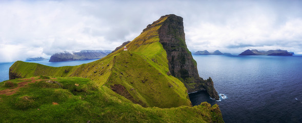 Small lighthouse located near huge cliffs on island of Kalsoy, Faroe Islands