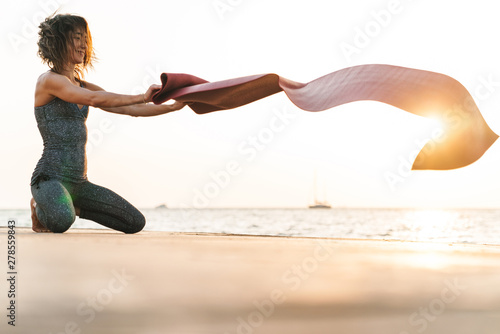 Photo of attractive sportswoman sitting on pier and putting yoga mat by seaside Tableau sur Toile