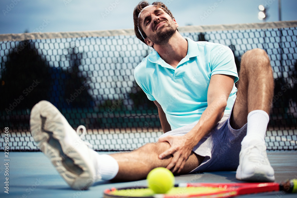 Fototapety, obrazy: Sports injury. Young tennis player touching his knee while sitting on the tennis court