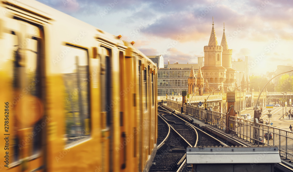 Fototapety, obrazy: Panoramic view of Berliner U-Bahn with Oberbaum Bridge in the background in golden evening light at sunset with dramatic clouds, Berlin Friedrichshain-Kreuzberg