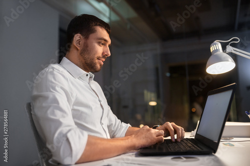 business, deadline and people concept - businessman with laptop computer working at night office