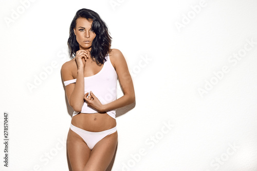 Fototapeta Sexy middle-aged slim woman in white underwear posing over a white studio background with copy space with a sultry look and sensual gestures obraz na płótnie