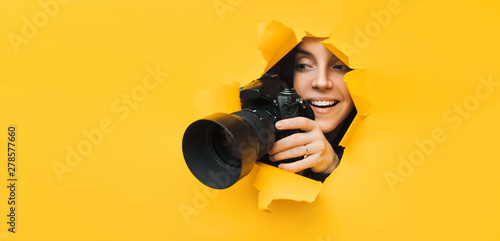 A young paparazzi girl holds a reflex camera and looks through a torn hole in yellow paper Canvas Print