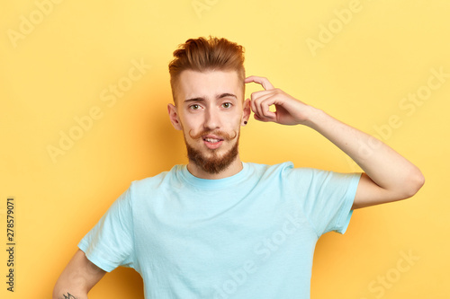 Foto Closeup portrait serious pensive man scratching head, thinking deeply about something, looking at the camera , isolated on yellow background