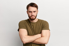 Angry Sad Unhappy Serious Man With Disapproving Expression On Face And Crossed Arms Looking At The Camera. Close Up Portrait. Isolated White Background. Negative Emotion