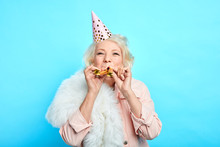 Happy Mature Childish Careless Woman In Party Hat Making A Noise In The Party. Isolated Blue Background, Studio Shot. Celebration, Happiness . Lifestyle