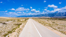 Long Deserted Road With Mountain And Blue Sky