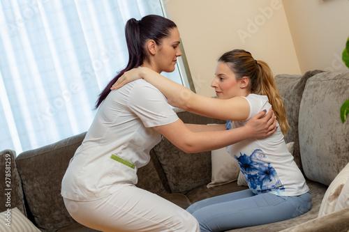 Fotografia Nurse assisting young disabled patient at home.