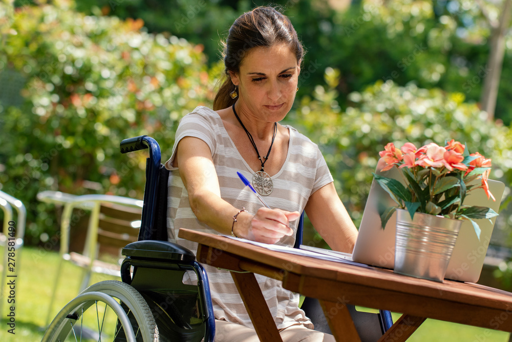 Fototapety, obrazy: Portrait of young disabled woman in wheelchair doing paper work in garden at table.