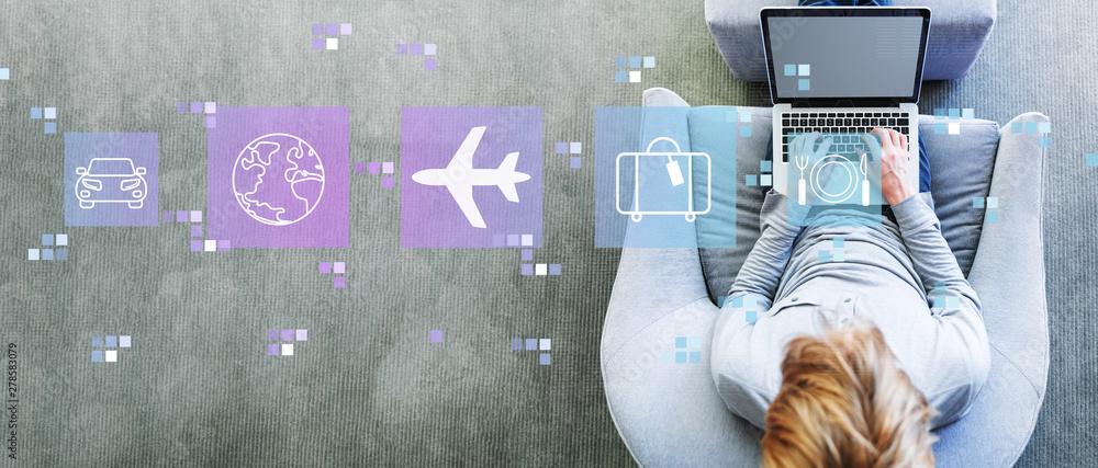 Fototapeta Airplane travel theme with man using a laptop in a modern gray chair