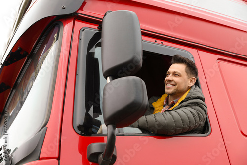 Photographie Portrait of happy driver in cab of modern truck