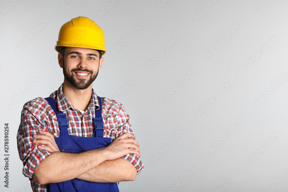 Fototapeta Portrait of construction worker in uniform on light background, space for text