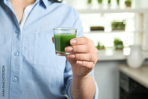 Fotografie, Obraz  Woman holding shot glass of wheat grass juice indoors, closeup