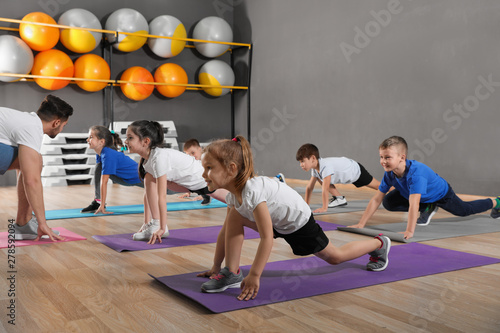 Foto  Cute little children and trainer doing physical exercise in school gym