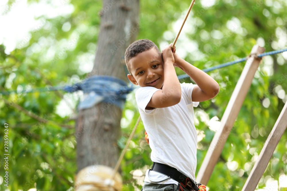 Fototapety, obrazy: Little African-American boy climbing in adventure park. Summer camp
