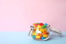 Jar Of Delicious Jelly Beans On Color Background. Space For Text